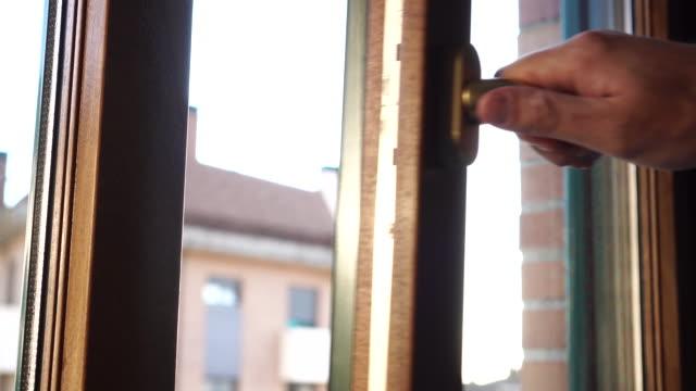 vídeos de stock e filmes b-roll de the man holding the golden handle closes the brown plastic window - obras em casa janelas