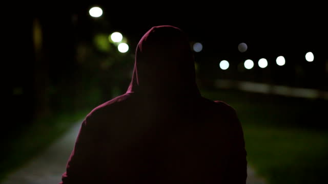 vídeos de stock e filmes b-roll de the man in a hood walking and smoking on the night street. slow motion - capuz