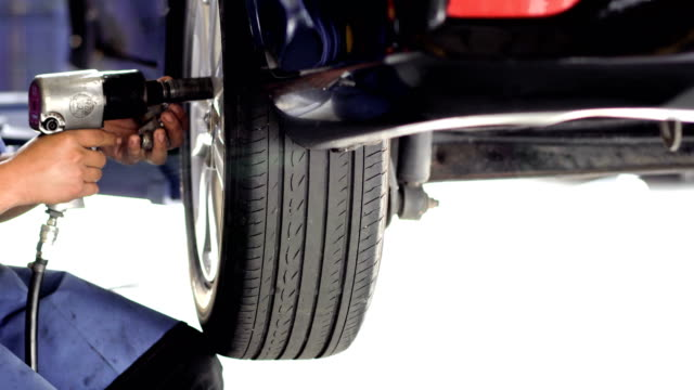 the man in the car-care center removes the wheel - truck tire video stock e b–roll
