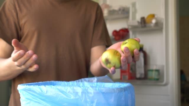 der mann in der küche. hausmüll aus frischem obst und gemüse im mülltonne - food stock-videos und b-roll-filmmaterial