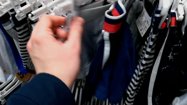 vidéos et rushes de l'homme dans le magasin choisit culottes sous-vêtements. la personne touche un boxeur. il ya une grande sélection de shorts dans différentes couleurs. un mâle avec sa main considère différents types de slips mâles de coton - homme slip