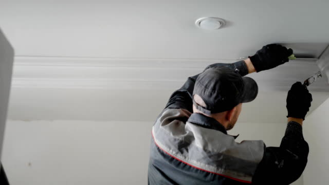 the man is doing repairs in the apartment, the person is painting with a tassel plaster molding on the ceiling - poliuretano polimero video stock e b–roll