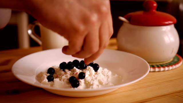 男は、スグリの果実で美味しい豆腐デザートを準備しています。デザートを作るシェフの手。カッテージ チーズと新鮮な果実。 - パフェ点の映像素材/bロール