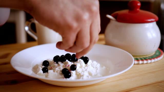 男は、スグリの果実で美味しい豆腐デザートを準備しています。デザートを作るシェフの手。カッテージ チーズと新鮮な果実。スローモーション。 - パフェ点の映像素材/bロール