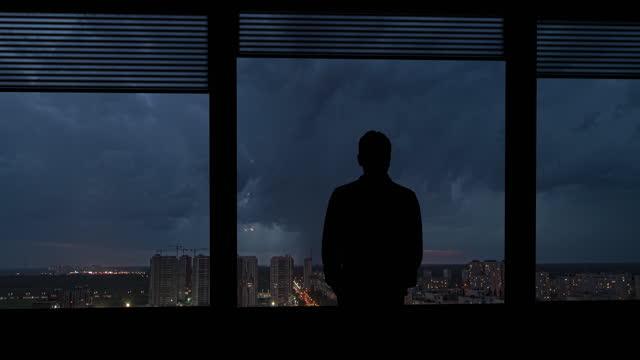 男は雨の多い街の背景の窓の近くに立っています。タイムラプス - 人の居住地点の映像素材/bロール