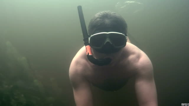 The man is swimming under the water video
