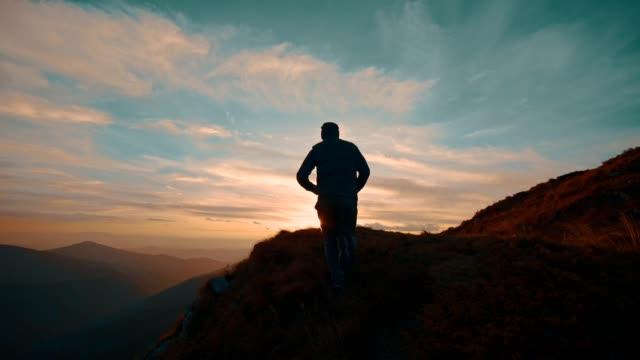 человек прыгает на гору против прекрасного заката. замедленное движение - достижение стоковые видео и кадры b-roll