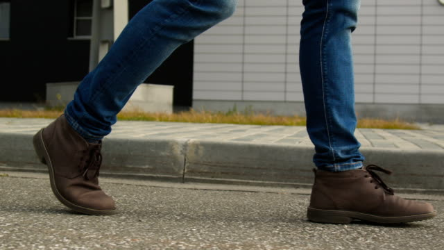 The man legs in shoes walk on the pavement closeup The one guy slowly confidence walks along the town footway in blue jeans and stylish leather shoe. Point of view on legs closeup. Spring cold weather, pedestrian goes past the building slow motion foot stock videos & royalty-free footage