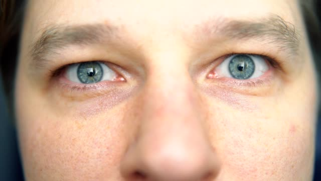 the man opens his eyes, close-up video