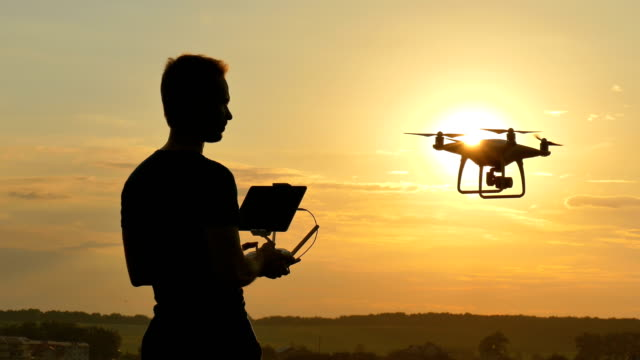 The man playing with a quadrocopter on the sunrise background The man playing with a quadrocopter on the sunrise background landing touching down stock videos & royalty-free footage