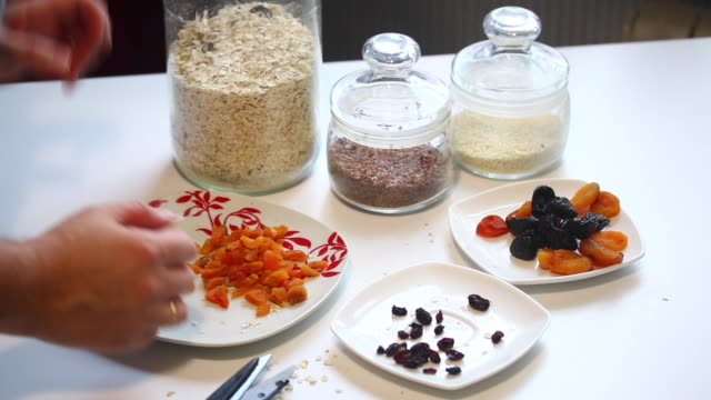The man prepares the ingredients for muesli at home. He adds dried apricots to oat flakes. video