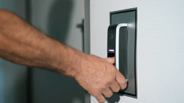 The man puts his finger on a fingerprint scanner which is designed to enter the door. Modern security technology in everyday lives of employees. Work of protection against burglary close up video