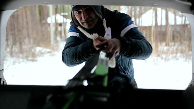 the man puts his skis inside the car. - sprzęt sportowy filmów i materiałów b-roll
