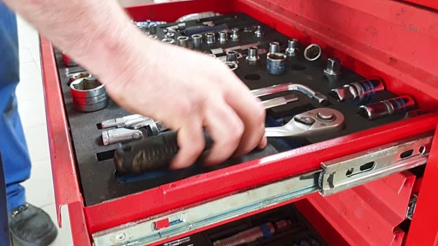 vídeos de stock e filmes b-roll de the man puts the tools into the holes in the tool box, red iron chest in a car workshop - fundo oficina