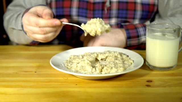 The man raises a spoon and sharply pushes the porridge back into the plate. Close-up of a male hand is driving a spoon on a plate with oatmeal. The man pushes the porridge and takes a glass of milk spoon stock videos & royalty-free footage