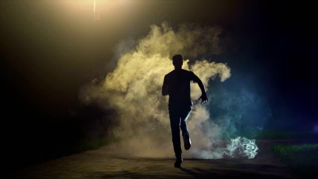 vídeos de stock e filmes b-roll de the man running in the cloud of smoke on the dark background, slow motion - fugir