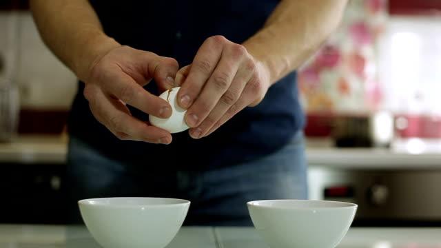 the man separates the yolk in the egg - нержавеющая сталь стоковые видео и кадры b-roll