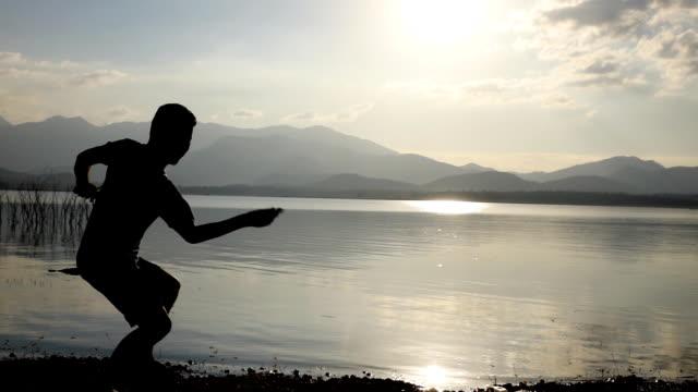 那人在湖邊跳石頭, 慢動作 - 石材 個影片檔及 b 捲影像