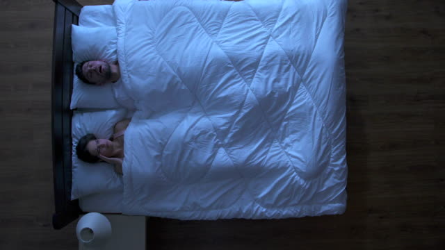 The man snore near woman in the bed. night time. view from above video