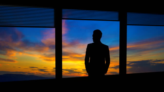 the man stand near a window on the cloud stream background. time lapse - man look sky scraper video stock e b–roll