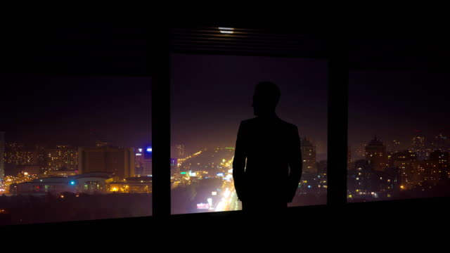the man stand near the window on a background of night city. time lapse - man look sky scraper video stock e b–roll