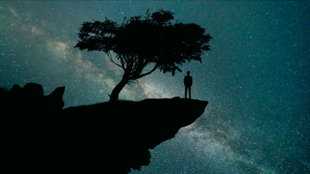 The man stand on the mountain on the starry sky background. evening night time