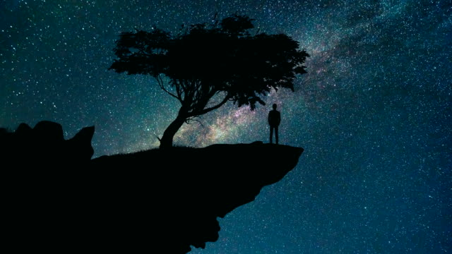 The man stand on the mountain on the starry sky background. time lapse