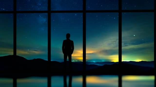 The man standing near panoramic window on a starry sky background. time lapse