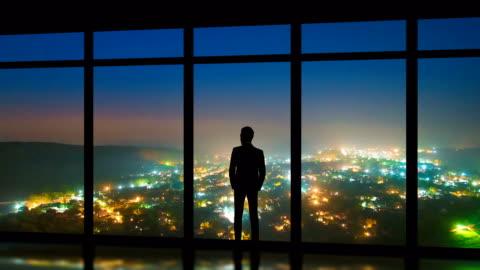der mann steht in der nähe von panoramafenstern auf dem nebligen stadt hintergrund. zeitraffer - betrachtung stock-videos und b-roll-filmmaterial