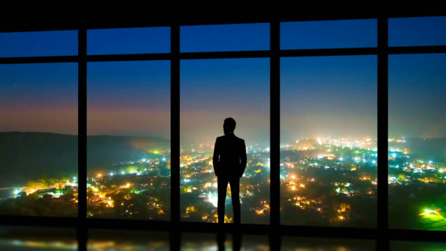the man standing near panoramic windows on the foggy city background. time lapse - только один мужчина стоковые видео и кадры b-roll