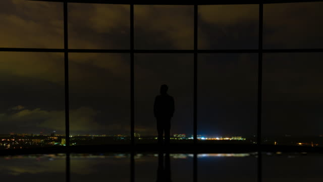 the man standing near the window on a city lightning background. time lapse - man look sky scraper video stock e b–roll
