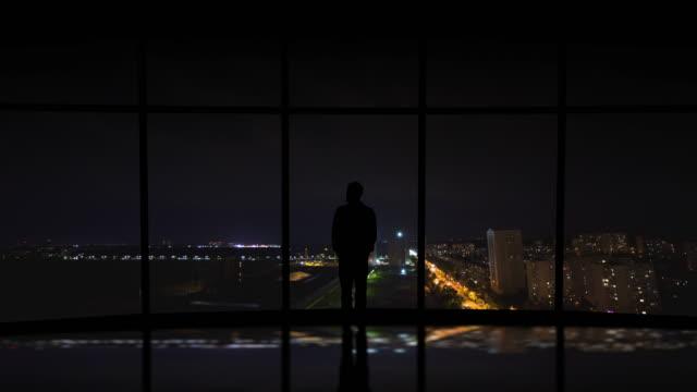 the man standing near the window on the city lightning background - man look sky scraper video stock e b–roll