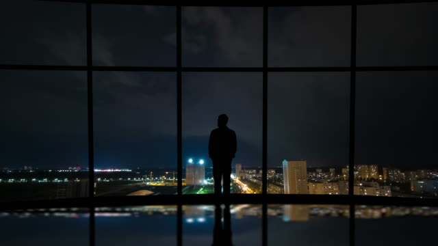 the man standing near the window on the city lightning background. time lapse - man look sky scraper video stock e b–roll