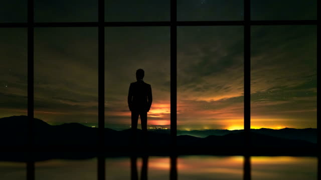 The man standing near window on a sky with stars background. time lapse