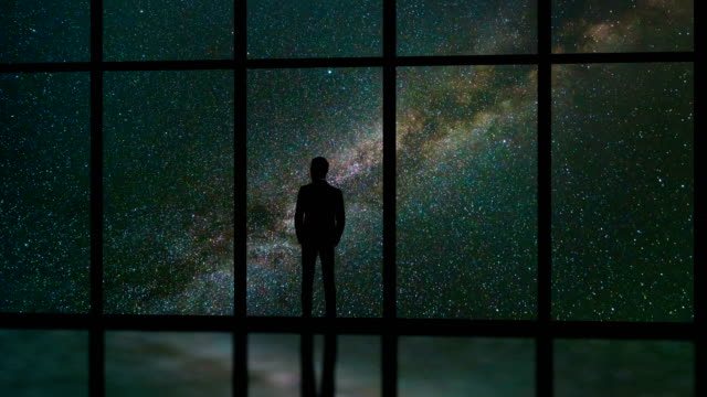 The man standing near window on a stars background. time lapse
