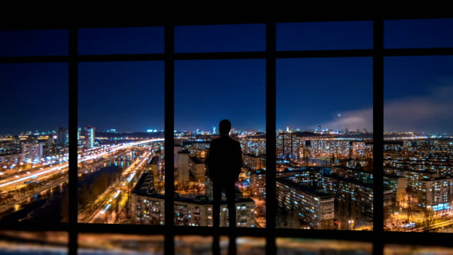 the man standing near windows on a night metropolis background. time lapse - business man стоковые видео и кадры b-roll