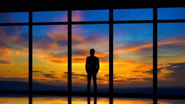 the man standing near windows on the sunrise background. time lapse - solo un uomo video stock e b–roll