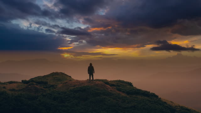 The man standing on a mountain against a picturesque cloud stream. time lapse The man standing on a mountain against a picturesque cloud stream. time lapse mountains in mist stock videos & royalty-free footage