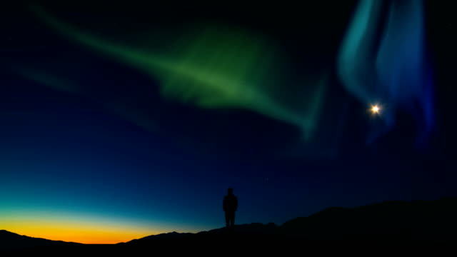 The man standing on a mountain against the sky with a northern light. time lapse