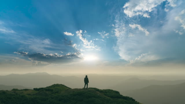 The man standing on a mountain on the bright sun background