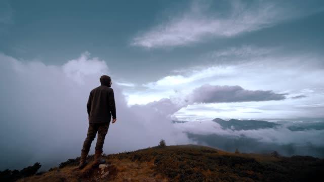 vídeos y material grabado en eventos de stock de el hombre de pie en una montaña en el fondo de la nube. cámara lenta - espalda humana