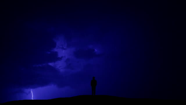 vídeos de stock e filmes b-roll de the man standing on the hill against the background of lightning - storm effects