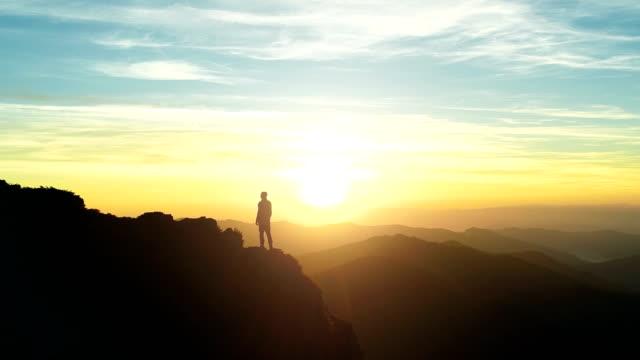 der mann, der auf dem berg steht und den sonnenuntergang genießt - horizont stock-videos und b-roll-filmmaterial