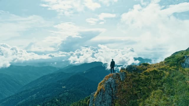 The man standing on the mountain cliff with a beautiful landscape The man standing on the mountain cliff with a beautiful landscape cliffs stock videos & royalty-free footage