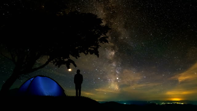 the man standing on the mountain near a camping tent. time lapse - astronomia video stock e b–roll