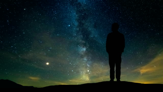 The man standing on the mountain on the starry sky background. time lapse