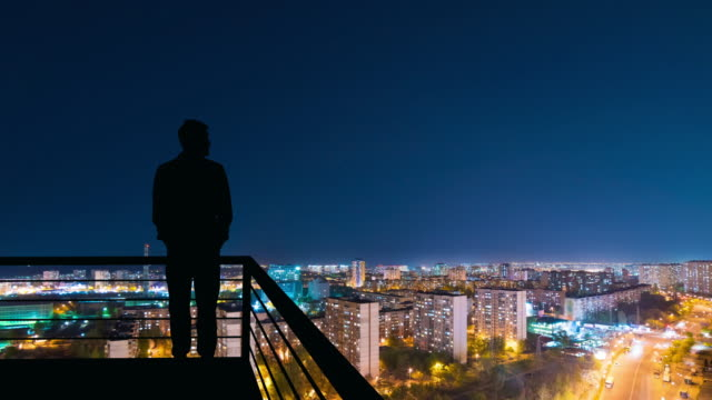 the man standing on the top of building on the night cityscape background - man look sky scraper video stock e b–roll