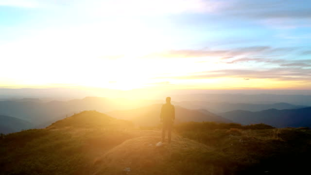 The man standing on the top of the mountain with a beautiful sunrise