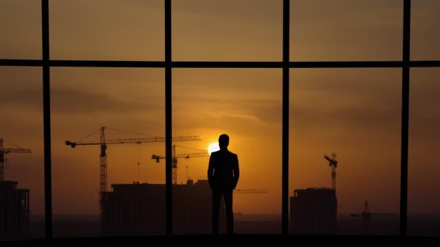 男は建物に対するパノラマの窓の近くに立っている - クレーン点の映像素材/bロール