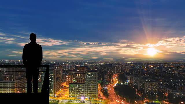 vídeos de stock, filmes e b-roll de o homem está na varanda do fundo da paisagem da cidade. hiperlapso - sol nascente horizonte drone cidade